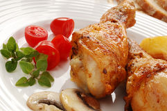 Roasted chicken legs. With vegetables royalty free stock images
