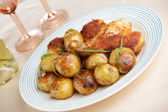 Roasted chicken legs with baked potatoes Royalty Free Stock Images