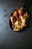 Roasted chicken legs with baked potatoes Stock Photography
