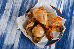 Roasted chicken legs on  blue plate. Stock Images