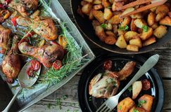 Roasted chicken legs and fried potatoes Stock Image