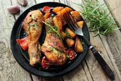 Roasted chicken legs. With fried potatoes and fresh herbs royalty free stock images