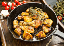 Roasted chicken legs with herbs and baked potatoes garnish Royalty Free Stock Photo