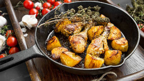 Roasted chicken legs with herbs and baked potatoes garnish Stock Images