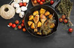Roasted chicken legs with herbs and baked potatoes garnish Stock Photos