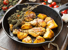 Roasted chicken legs with herbs and baked potatoes garnish Stock Image