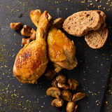 Roasted chicken legs. High-angle shot of some pieces of roasted chicken, some slices of bread and some roasted mushrooms on a slate tray sprinkled with different royalty free stock images