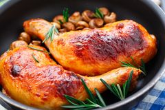 Roasted chicken legs. With mushrums in a pan royalty free stock photography