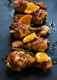 Roasted chicken legs, oranges and rosemary on the black background. Cooked with sauce from mustard, orange, honey and olive oil Royalty Free Stock Photos