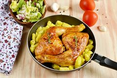 Roasted chicken legs with potatoes Stock Image