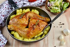 Roasted chicken legs with potatoes Royalty Free Stock Images