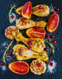 Roasted chicken legs, red oranges, cranberries, garlic and rosemary on the black background Royalty Free Stock Photo