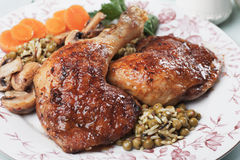 Roasted chicken legs. With rice and green peas, classic of traditional cuisine Stock Photos