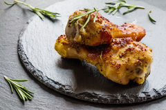 Roasted chicken legs and rosemary on the black background. Cooked with sauce from mustard, orange, honey and olive oil Stock Photo