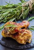 Roasted chicken legs and rosemary on the black background. Cooked with sauce from mustard, orange, honey and olive oil Royalty Free Stock Image