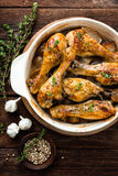 Roasted chicken legs on rustic wooden background, top view Stock Photos