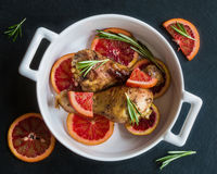 Roasted chicken legs on slices of red oranges in white baking dish. Black slate background. Cooked with the sauce: orange juice, mustard, olive oil and honey Stock Image