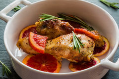 Roasted chicken legs on slices of red oranges in white baking dish. Black slate background. Cooked with the sauce: orange juice, mustard, olive oil and honey Stock Photography