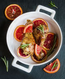 Roasted chicken legs on slices of red oranges in white baking dish. Black slate background. Stock Photos