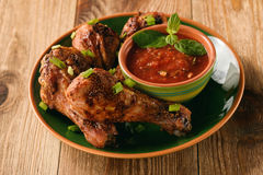 Roasted chicken legs and tomato sauce on wooden background. Stock Image