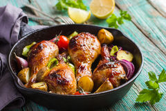 Roasted chicken legs with vegetables. On cast iron pan royalty free stock image