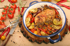 Roasted chicken legs with vegetables and herbs on wooden backgro Royalty Free Stock Photos