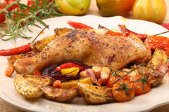 Roasted chicken legs with vegetables and herbs Stock Photo