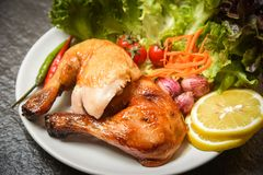 Roasted chicken legs white plate with lemon chilli spicy herbs spices and salad lettuce vegetable. Roasted chicken legs on white plate with lemon chilli spicy royalty free stock images