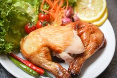 Roasted chicken legs on white plate with lemon chilli spicy herbs spices and salad lettuce vegetable. Carrot shallot tomato on dining table food / Grilled royalty free stock images