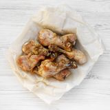 Roasted chicken legs on a white wooden background, top view. Flat lay, overhead. From above royalty free stock photography