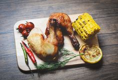 Roasted chicken legs on wooden cutting board with corn lemon chilli spicy herbs spices and tomato on dining table food - Grilled royalty free stock images
