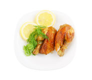 Roasted chicken with lemon and greens on plate Royalty Free Stock Photos