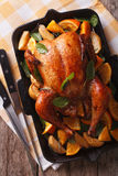 Roasted chicken with oranges close-up in a pan. vertical top vie Royalty Free Stock Images