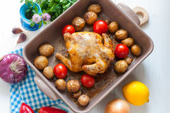 Roasted chicken with potato and tomato in ceramic dish, top view Royalty Free Stock Image