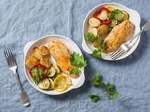 Roasted chicken provencal with zucchini, squash, potatoes. Delicious healthy lunch on a blue background. Top view stock photography