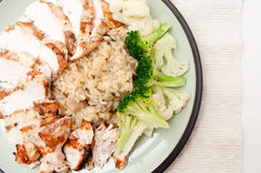 Roasted chicken and risotto. Roasted chicken sliced and presented with mushroom risotto and broccoli and cauliflower. A heart healthy meal Royalty Free Stock Image
