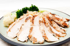 Roasted chicken and risotto. Roasted chicken sliced and presented with mushroom risotto and broccoli and cauliflower. A heart healthy meal Stock Image