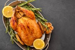 Roasted chicken with rosemary served on a metal plate with lemon on black table. Christmas turkey. Copy space. Top view. royalty free stock photography