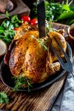 Roasted chicken with rosemary served on black plate with sauces on wooden table, close up royalty free stock photos