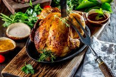 Roasted chicken with rosemary served on black plate with sauces on wooden table, close up stock photos
