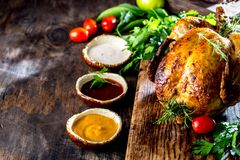 Roasted chicken with rosemary served on black plate with sauces on wooden table, top view. stock image