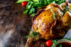 Roasted chicken with rosemary served with sauces on wooden board, selective focus, copy space stock photography