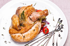 Roasted chicken with rosemary in a white plate stock photography