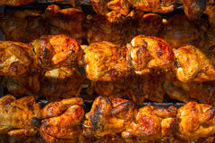 Roasted chicken in a row turning on a roaster. Roasted chicken in a row turning at industrial roaster royalty free stock photo