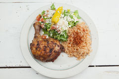 Roasted chicken with saffron rice and greek salad Royalty Free Stock Photos