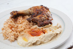 Roasted chicken with saffron rice and hummus Royalty Free Stock Photo