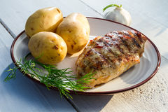 Roasted chicken served with potatoes and dill Royalty Free Stock Image