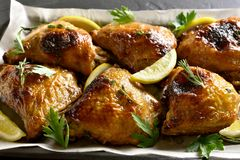 Roasted chicken thighs. Close up of roasted chicken thighs on baking tray stock image