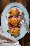 Roasted chicken thighs with olives and red onion. On brown wooden background Royalty Free Stock Images