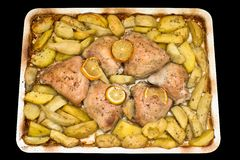 Roasted chicken thighs with potatoes and lemon. Stock Image